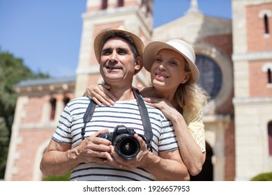 a middle-aged couple standing taking photographs on their camera