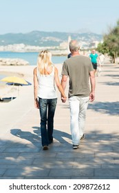 Middle-aged couple walking on a seafront promenade walking away from the camera hand in hand in the hot summer sunshine