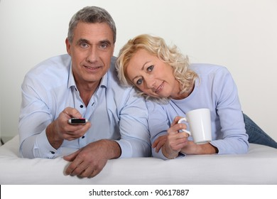 Middle-aged couple watching television in bed