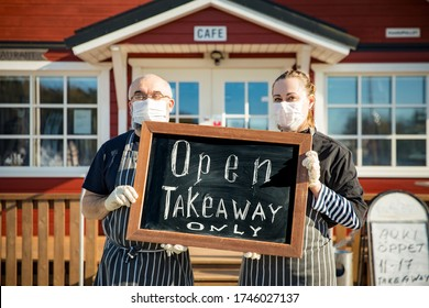 """A middle-aged couple wearing protective masks standing in front of the restaurant and holding a """"takeaway only"""" sign. Small business during coronavirus quarantine"""