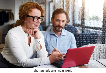 Middle-aged couple working on laptop and taking notes