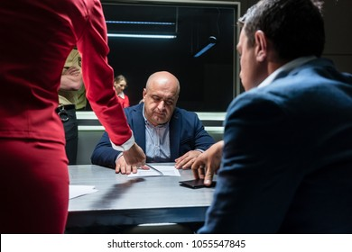 Middle-aged defendant or witness counseled by the lawyer to sign an official statement in front of the prosecutor, during a criminal investigation in the police station