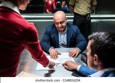 Middle-aged defendant or witness, counseled by the lawyer to sign an official statement in front of the prosecutor during a criminal investigation in the police station