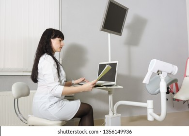 Middle-aged doctor in a white coat studying the results of colposcopy. Modern methods of diagnosis of gynecological diseases