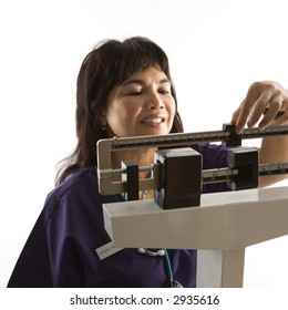 Middle-aged female Filipino nurse reading weight on scale.