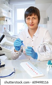 Middle-aged female scientist or tech looks at the camera and shows a handful of plastic tubes for medical samples