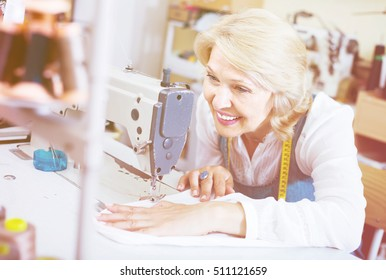 middle-aged female tailor using sewing machine at workshop