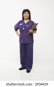 Middle-aged Filipino woman dressed in scrubs with stethoscope and clipboard.