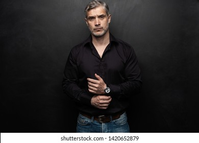 Middle-aged good looking man posing in front of a black background with copy space