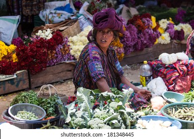 Middle-aged indigenous woman sells vegetables and flowers at traditional weekly market in Chichicastenango (Chichi), Guatemala.