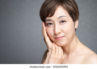 Middle-aged Japanese woman with both hands on her cheeks