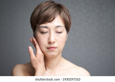 Middle-aged Japanese woman holding her cheeks with the back of her hand