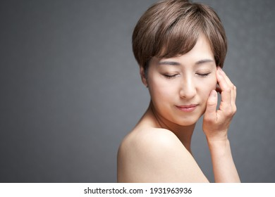 A middle-aged Japanese woman who puts her hand on her cheek and closes her eyes