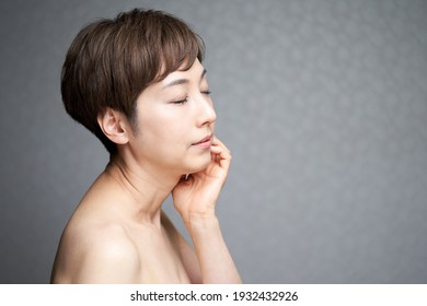 A middle-aged Japanese woman who puts her hand on her cheek and turns to the side