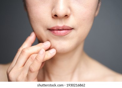 Middle-aged Japanese woman worried about wearing a cheek stick