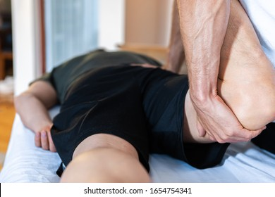 A middle-aged male getting a relaxing leg massage after hard work and training at the gym. Close-up view of masseur hands giving massage therapy