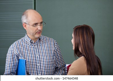 Middle-aged male lecturer and a young female student in a discussion standing close together in front of a blackboard chatting