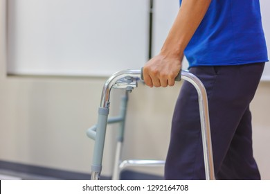 Middle-aged male patient are using walkers to practice walking after surgery. Medical and healthcare concept. Image with copy space for text