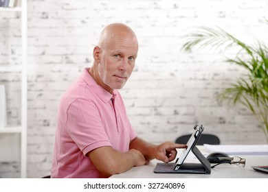 a middle-aged man alone, sitting with a tablet