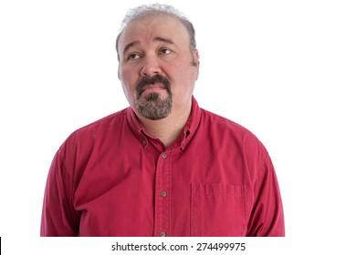 Middle-aged man with baldness and goatee beard wearing a dark red shirt while looking up to the left with a sad and depressed facial expression, isolated portrait on white