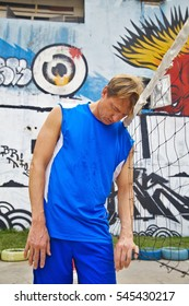 Middle-aged man in blue sports clothing in an urban setting clothing is leaning his head against a volleyball net after having lost a game.