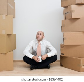 A middle-aged man with a coffee cup sitting in between stacked cardboard boxes containing his belongings, after shifting in a new house.