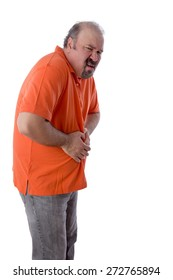 Middle-aged man with constipation grimacing in pain as he clutches his stomach in discomfit due to compaction of his feces and inability to enjoy a regular bowel movement