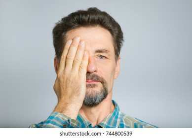 middle-aged man covers eyes with hands, does not see, studio photo is isolated on a white background