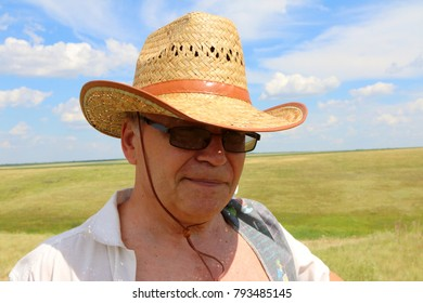 Middle-aged man in a cowboy hat and glasses enjoying the nature freedom