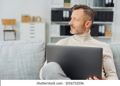 Middle-aged man daydreaming or thinking of future aspirations while sitting on sofa with his laptop in a modern office