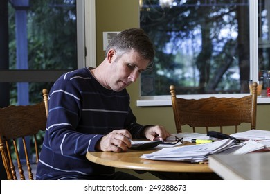 A middle-aged man doing paperwork on a table at home.