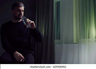 Middle-aged man drinking and smoking alone in a room