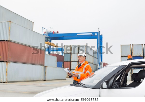 Middle-aged man examining cargo in shipping yard