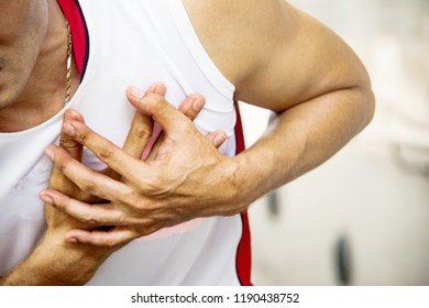Middle-aged man exercising outdoors, having a sudden chest pain, using his hand in the heart with pain and suffering.