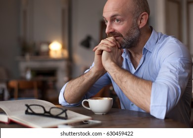 A middle-aged man is having breakfast in the room. On the table is a cup of tea and a book. He looks thoughtfully aside, planning the day.