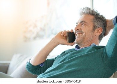 Middle-aged man at home talking on phone