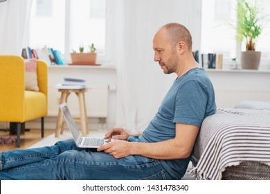Middle-aged man in jeans sitting on the floor with legs outstretched working on a laptop computer leaning against a sofa