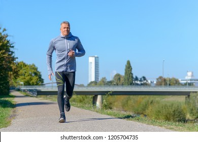 Middle-aged man jogging along alley in park on sunny day