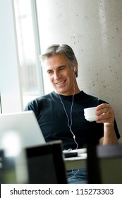 Middle-aged man listening to music sitting with his laptop in cafe
