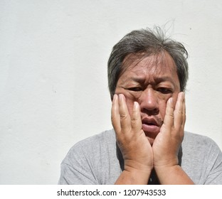The middle-aged man looks depressed and has gray hair, Asian men use his palms closed on cheek from the pain of Trigeminal Neuralgia , The human face show distress and sadness, Depression patients