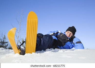 Middle-aged man lying in snow