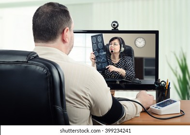 Middle-aged man measures his blood pressure in front of virtual doctor. In the meantime, telemedicine physician is carefully looking at his brain x ray picture in the monitor. Horizontal shot