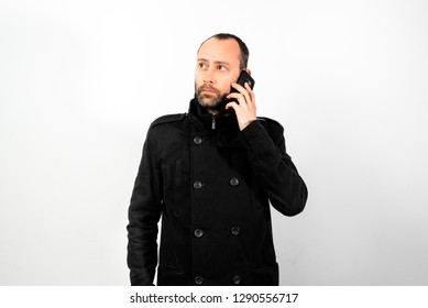 Middle-aged man with overcoat listens attentively to a conversation on his mobile phone, isolated on white.