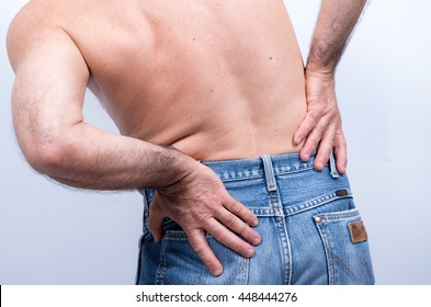middle-aged man with pain in the lumbar region pushes  to relieve it