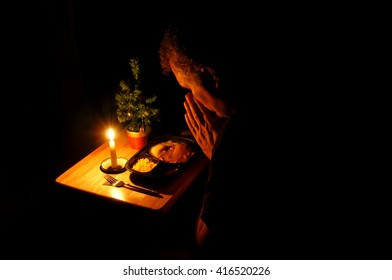 Middle-aged man praying over a candle lit TV dinner at Christmas time.