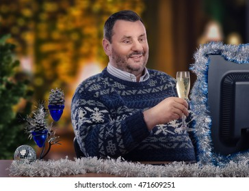 Middle-aged man proposes Christmas toast with glass of white wine during on-line video chat. Bearded man in Scandinavian sweater sits at the desk with tinsel garlands.