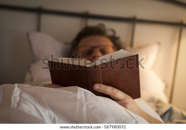 Middle-aged man is reading a book on his bed