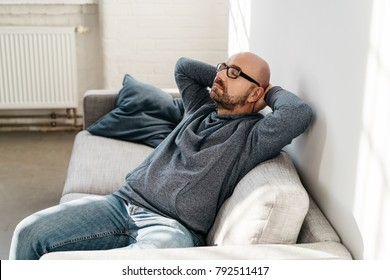 Middle-aged man relaxing or daydreaming while sitting on the couch with eyes closed and hands behind head indoors