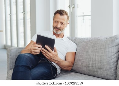 Middle-aged man relaxing on a sofa with a tablet computer smiling quietly as he reads something on the screen in a low angle view with copy space