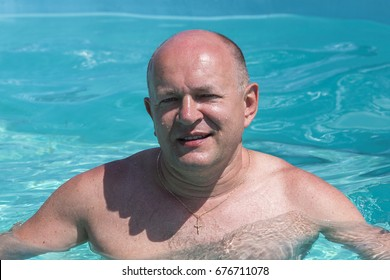 Middle-aged man relaxing in swimming pool, close up